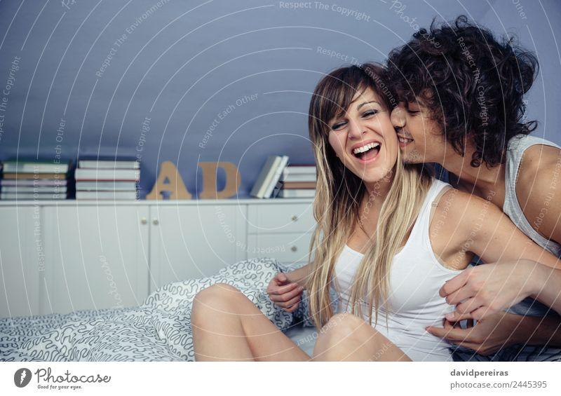 Mann küsst und kitzelt die Frau, die lacht. Lifestyle Freude Glück schön Erholung Spielen Schlafzimmer Erwachsene Paar Küssen Lächeln lachen Liebe sitzen