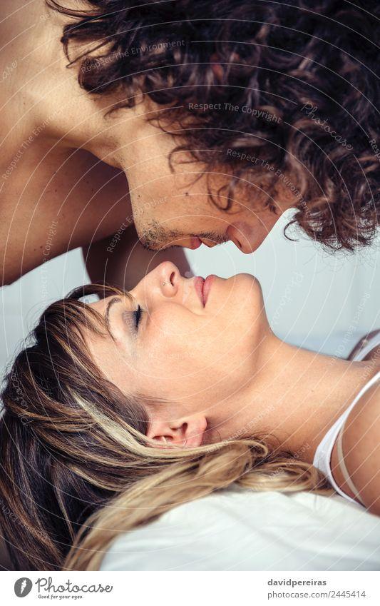 Junger Mann küsst die schöne Frau, die auf dem Bett liegt. Lifestyle Glück Erholung Schlafzimmer Erwachsene Familie & Verwandtschaft Paar Küssen Liebe schlafen