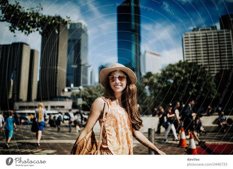 Eine süße lächelnde Frau mit Hut und Sonnenbrille geht auf der Straße mit dem Stadtbild von Sydney im Hintergrund. Lifestyle kaufen Stil Freude schön