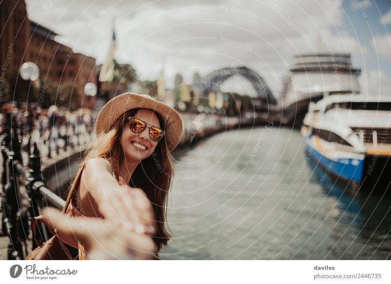 Süße Frau mit Hut und Sonnenbrille, die ihren Freund in der Stadt Sydney, Australien, an der Hand hält. Lifestyle Freude Ferien & Urlaub & Reisen Ausflug