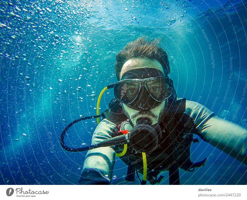 Mann mit Tauchausrüstung taucht im Meer und schaut in eine Kamera mit blauem Wasserhintergrund. Lifestyle exotisch Freude Freizeit & Hobby