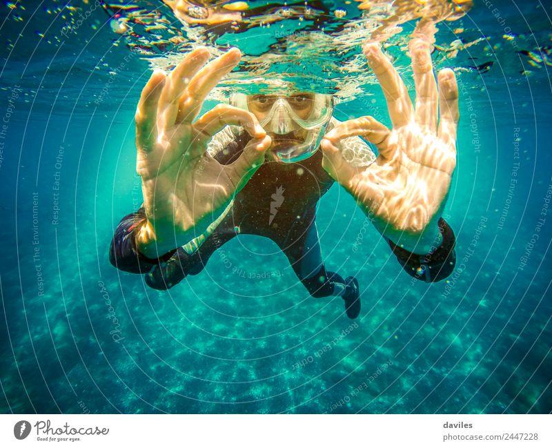 """Unterwasserporträt eines Mannes, der im Meer taucht, in die Kamera schaut und mit beiden Händen das """"ok""""-Zeichen macht. Lifestyle Freude Freizeit & Hobby"""