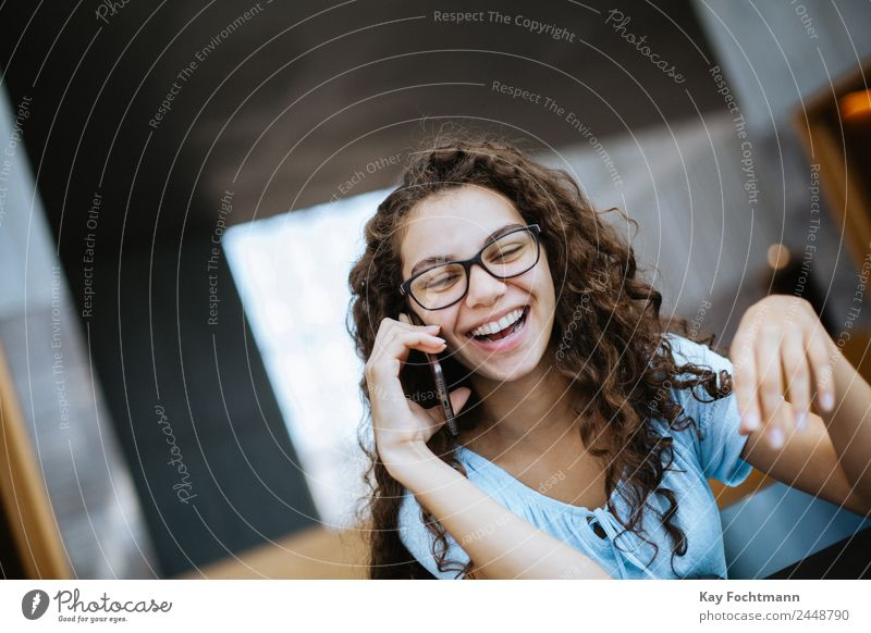 Junge Frau mit lockigem Haar lacht während eines Telefonats Lifestyle Freude schön Wohlgefühl Freizeit & Hobby Häusliches Leben Wohnung lernen Student Hörsaal