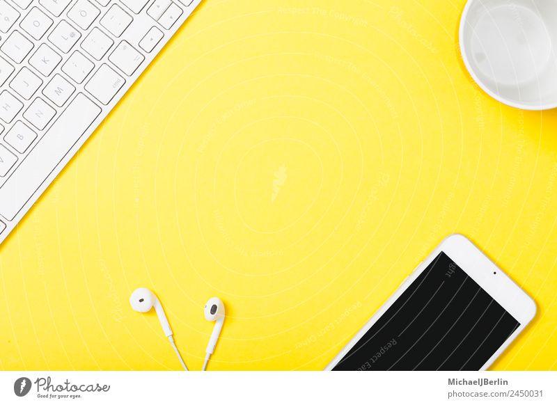 Handy und Kopfhörer auf gelbem Hintergrung Tasse Büro Tastatur Fröhlichkeit Hintergrundbild clever Symbole & Metaphern Arbeit & Erwerbstätigkeit Farbfoto