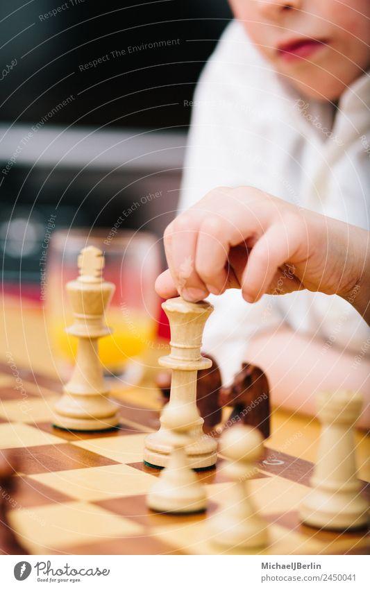 Junge im Grundschulalter spielt Schach Freude Freizeit & Hobby Spielen Wohnung Raum Denken Schulkind Schachbrett Farbfoto Innenaufnahme Nahaufnahme