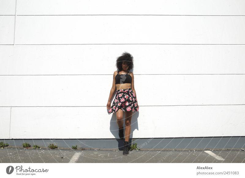 Frau vor einer weißen Wand Stil schön Leben Junge Frau Jugendliche Erwachsene 18-30 Jahre Schönes Wetter Mauer Fassade Parkplatz Rock Top schwarzhaarig