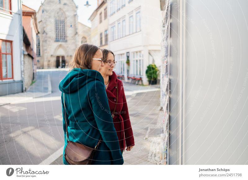 Zwillinge schauen sich Laden mit Postkarten an Mensch Jugendliche Junge Frau blau rot Freude Lifestyle feminin Glück Tourismus Zusammensein Ausflug paarweise
