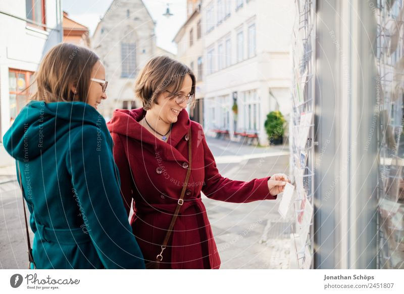 Zwillinge schauen sich Postkarten an Mensch Jugendliche Junge Frau blau rot Freude Lifestyle feminin lachen Glück Tourismus Zusammensein Ausflug Lebensfreude