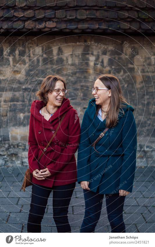 Zwillinge albern vor einer Wand rum Mensch Jugendliche Junge Frau blau rot Freude Lifestyle Leben lustig feminin lachen Stil Glück Zusammensein paarweise Rücken