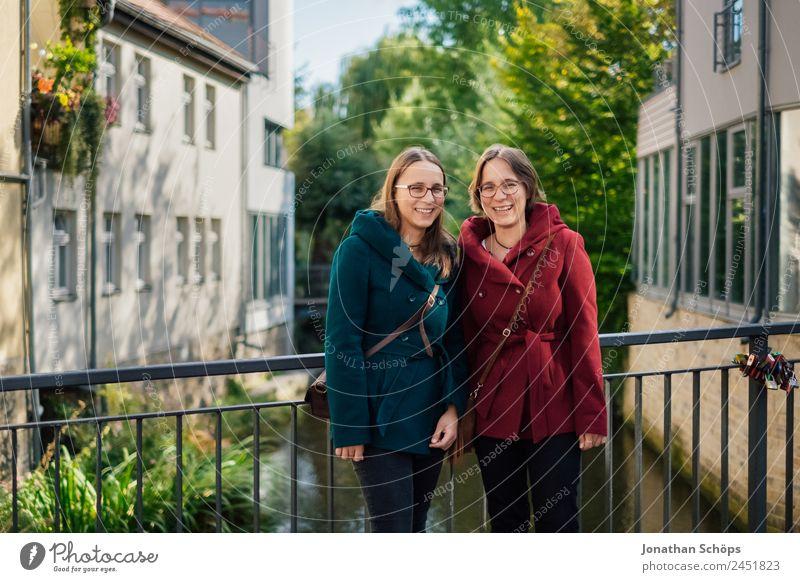 Zwillinge stehen auf einer Brücke am Geländer Mensch Jugendliche Junge Frau blau rot Freude Lifestyle Leben feminin lachen Stil Glück Tourismus Menschengruppe