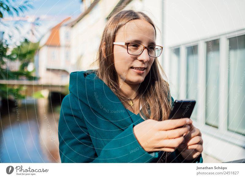 junge Frau mit Smartphone in der Hand am Fluss Mensch Jugendliche Junge Frau blau rot ruhig Freude Lifestyle Leben feminin lachen Stil Glück Tourismus