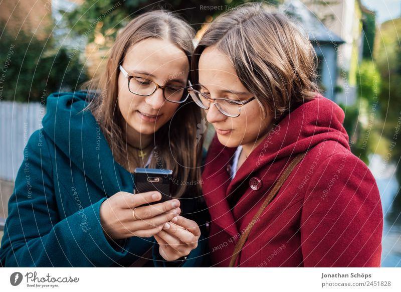 Zwillinge schauen auf ein Smartphone Mensch Jugendliche Junge Frau Freude Lifestyle lustig feminin Stil Glück Zusammensein Ausflug Zufriedenheit paarweise