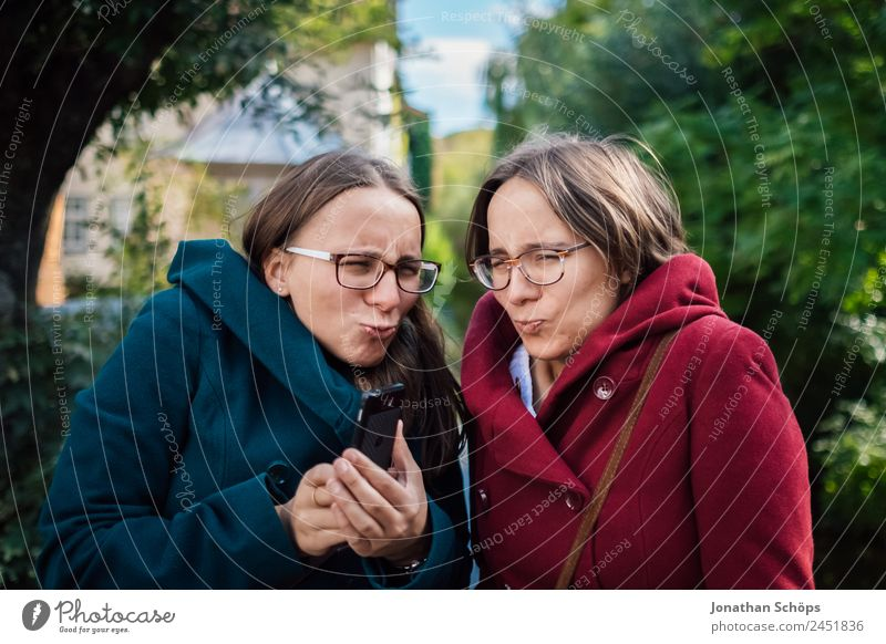 lustige Zwillingsschwestern machen ein Selfie mit dem Smartphone Lifestyle Freude Glück Mensch feminin Junge Frau Jugendliche Geschwister Schwester 2