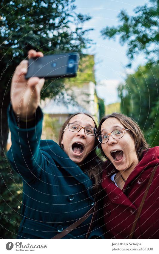 lustige Zwillingsschwestern machen ein Selfie mit dem Smartphone Lifestyle Freude Glück Mensch feminin Junge Frau Jugendliche Geschwister Schwester Leben 2