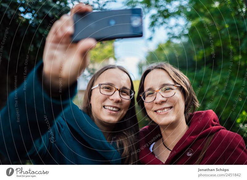 fröhliche Zwillingsschwestern machen ein Selfie mit dem Smartphone Lifestyle Stil Freude Glück Mensch feminin Junge Frau Jugendliche Geschwister Schwester Leben