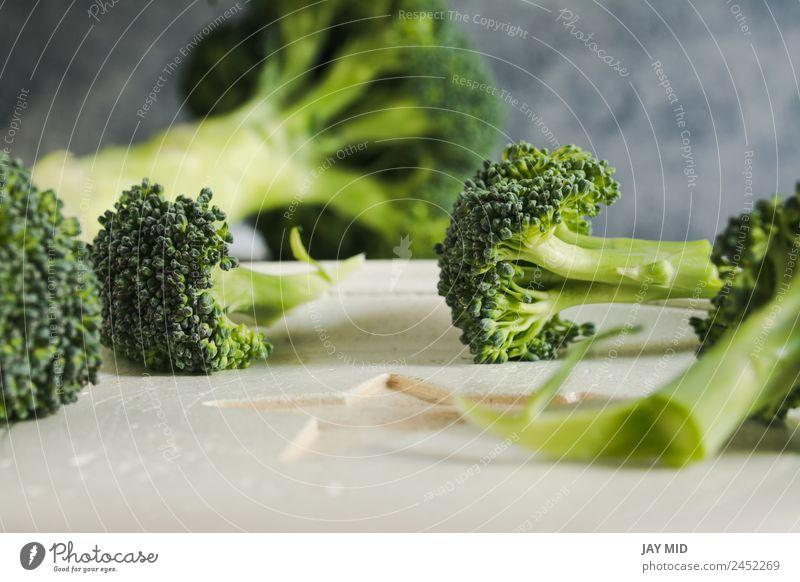 Kleine Stücke roher Brokkoli auf weißem Holz, Nahaufnahme Lebensmittel Gesunde Ernährung Speise Spielfigur Gesundheit Detailaufnahme frisch grün Diät Gemüse