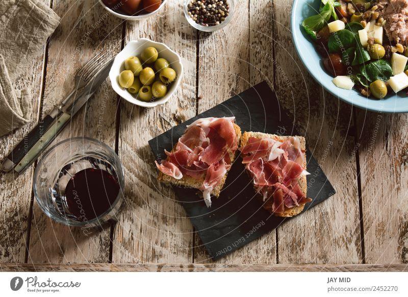 Köstliche Vorspeise mit spanischem Schinken und Salat Spanisch Brot Toastbrot Amuse-Gueule Kochen geschnitten Belegtes Brot iberisch Schweinefleisch Mittagessen