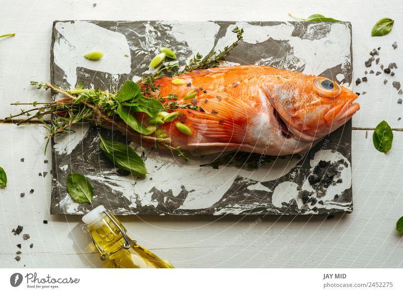 Rohe rote Skorpionsfische auf Marmortisch. Skorpionfisch roh kochen & garen Fisch Lebensmittel Zutaten Kräuter & Gewürze Steinplatten Ernährung orange Rosmarin