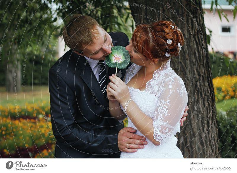 die Braut und der Bräutigam beißen einen Lolli. Lifestyle Freizeit & Hobby Spielen Hochzeit maskulin feminin Familie & Verwandtschaft Partner Erwachsene 2
