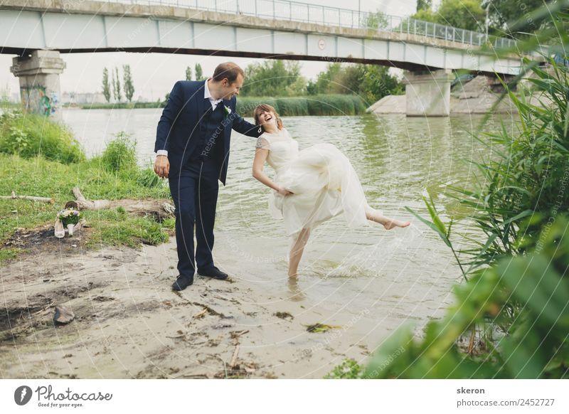 der Bräutigam hält eine lächelnde Braut, die ihre Füße in den Fluss benetzt. Lifestyle Freizeit & Hobby Sommer Wellen Valentinstag Hochzeit maskulin feminin