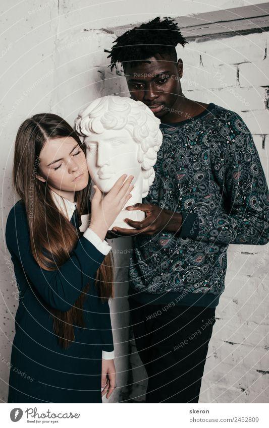 junges Mädchen und ein großer Afrikaner, der eine Skulptur in den Händen hält. Mensch maskulin feminin Junge Frau Jugendliche Junger Mann Freundschaft Paar
