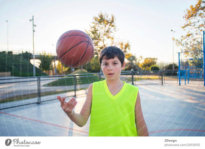 Schöne junge Teenager-Modell trägt eine gelbe ärmellose und hält den Ball auf dem Platz Lifestyle Glück Gesicht Erholung Freizeit & Hobby Spielen Sport Erfolg