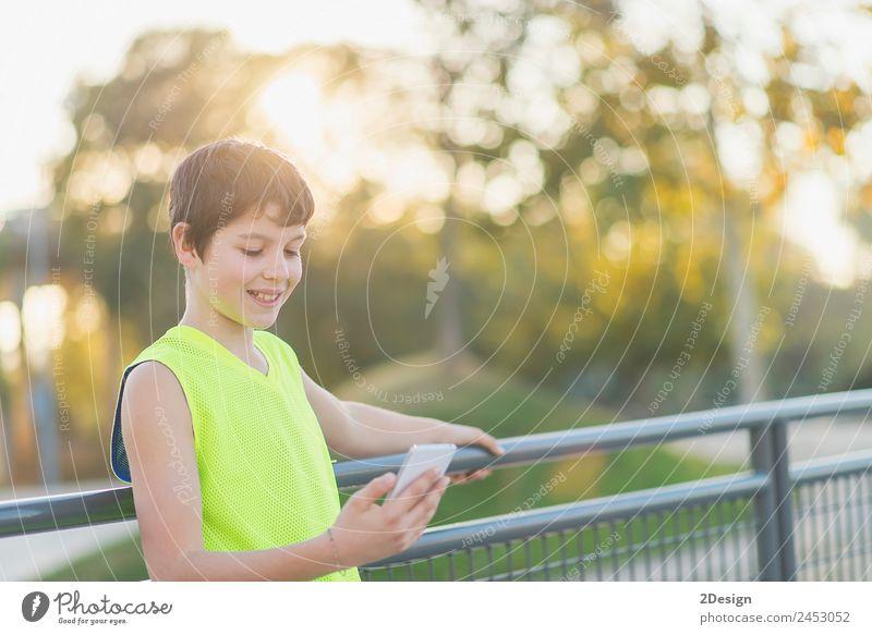Teenager lächelnd, der sein Smartphone auf einem Basketballplatz aussieht. Lifestyle Stil Freude Glück Freizeit & Hobby Dekoration & Verzierung Schule Studium
