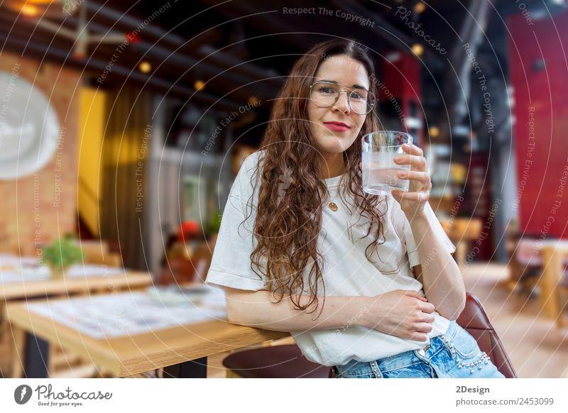 Hübsche junge Frau hält ein Glas Wasser. Frühstück Getränk trinken Kaffee Lifestyle Glück schön Gesundheitswesen Erholung Sommer Stuhl Tisch Restaurant Mensch