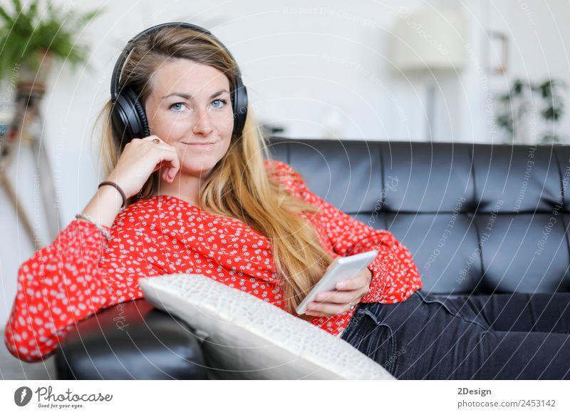 Glückliche Frau, die mit Kopfhörern Musik hört. Lifestyle Freude schön Erholung ruhig Freizeit & Hobby Spielen Sofa Telefon PDA Technik & Technologie Internet