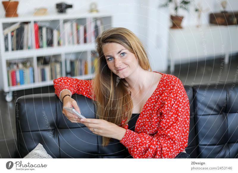 Glückliches Mädchen mit einem Smartphone, das zu Hause auf einer Couch sitzt. Lifestyle kaufen schön Spielen Dekoration & Verzierung Business Telefon Handy PDA
