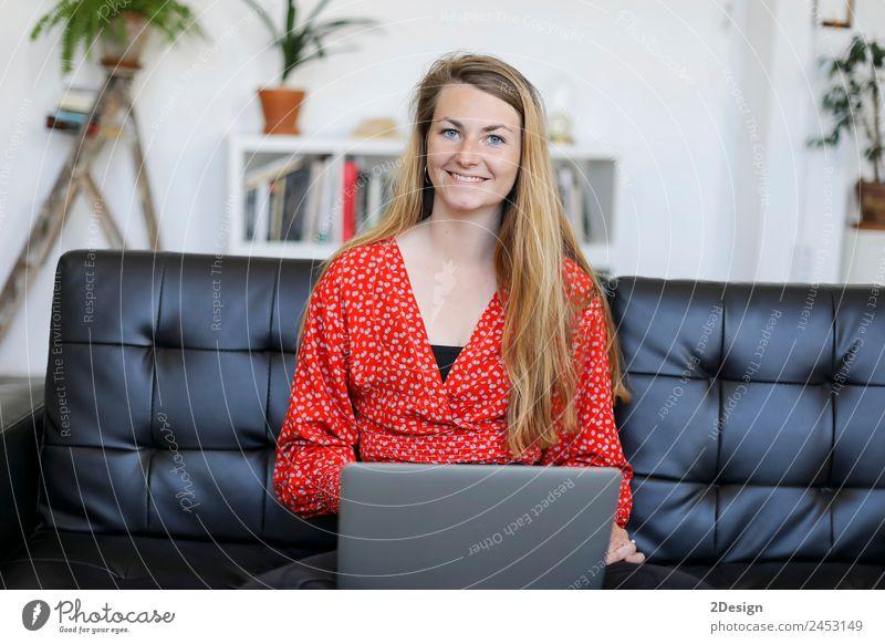 Unternehmerin in rotem Hemd arbeitet mit einem Laptop und sitzt zu Hause auf einer Couch kaufen Glück schön Sofa Schule lernen Studium Arbeit & Erwerbstätigkeit