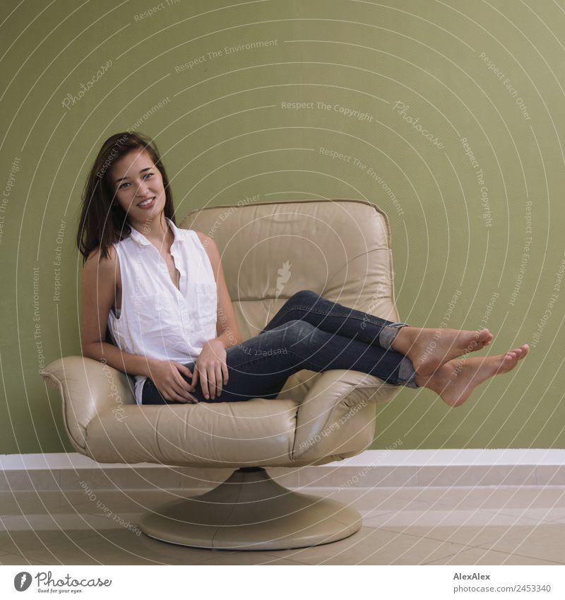 Frau im Sessel Lifestyle Stil schön Leben Junge Frau Jugendliche 18-30 Jahre Erwachsene Jeanshose Bluse Barfuß schwarzhaarig langhaarig Lächeln sitzen