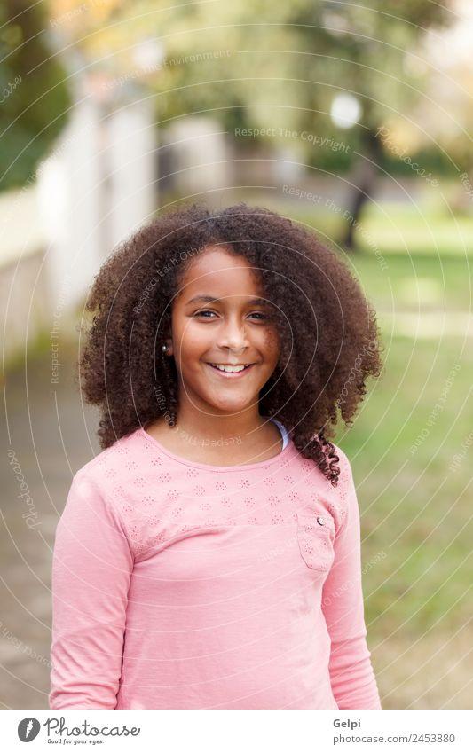 Süßes afroamerikanisches Mädchen lächelnd auf der Straße mit Afrohaar. Freude Glück schön Winter Kind Mensch Kleinkind Kindheit Natur Park Afro-Look Lächeln