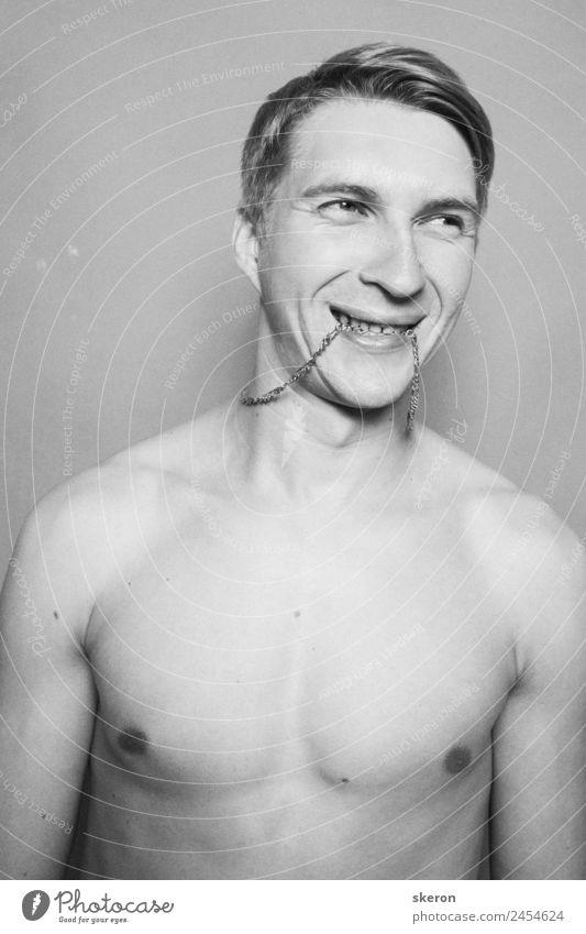 Der junge Mann hält eine Kette zwischen den Zähnen. Mensch maskulin Junger Mann Jugendliche Erwachsene Körper Haare & Frisuren Mund Lippen 1 18-30 Jahre