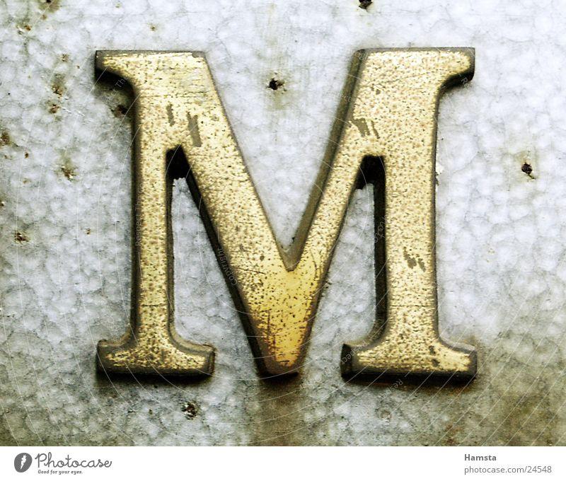 Golden M Buchstaben Serife obskur gold Metall Licht von Seite Prägung Stanzung