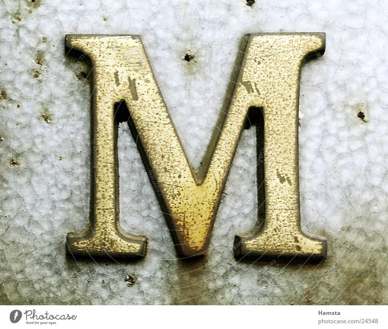 Golden M Metall gold Buchstaben obskur Serife Prägung