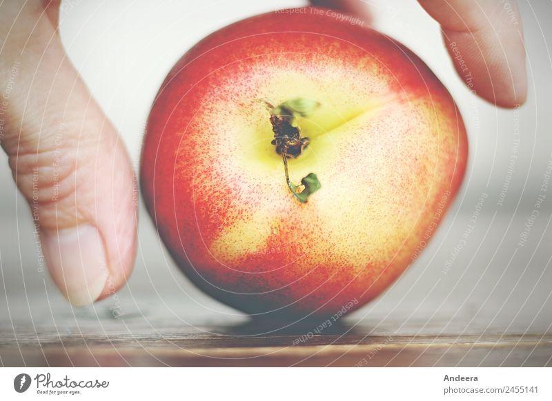 Finger legen eine Nektarine auf eine Tischplatte Lebensmittel Frucht Ernährung Vegetarische Ernährung Fasten Slowfood Fingerfood Vegane Ernährung Gesundheit