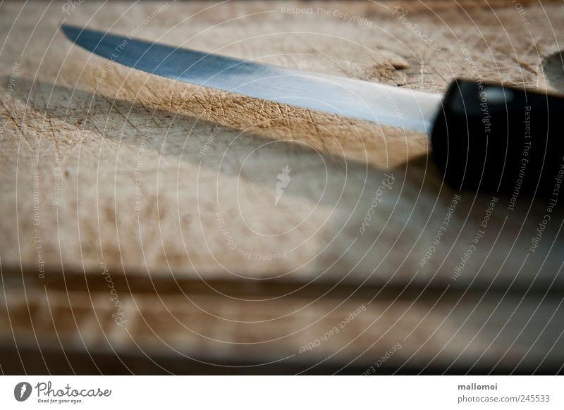 Mackie Messer Schneidebrett Holzbrett Manuelles Küchengerät alt braun schwarz silber Klinge matt geschnitten Furche Spitze Metall gefährlich Risiko Farbfoto