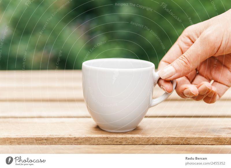 Frau Hand, die eine Tasse Kaffee von einem Holztisch im Garten aufzieht. Tisch Hintergrundbild grün Frühstück Morgen Café Licht weiß trinken Espresso