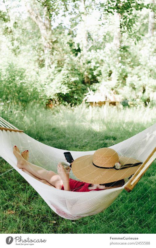 Young woman relaxing in a hammok Junge Frau Jugendliche Erwachsene 1 Mensch 18-30 Jahre 30-45 Jahre Natur Erholung Garten Hängematte Pause Schatten sommerhut