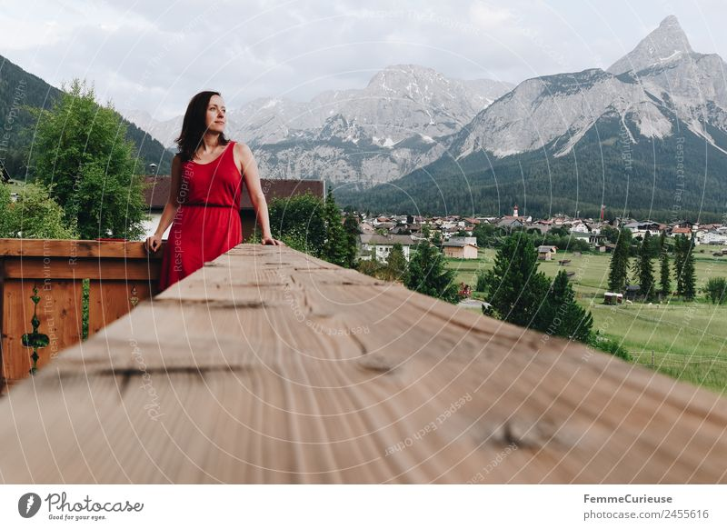 Young woman enjoying the view of the alps from a balcony feminin Junge Frau Jugendliche Erwachsene 1 Mensch 18-30 Jahre 30-45 Jahre Erholung Kleid rot Balkon