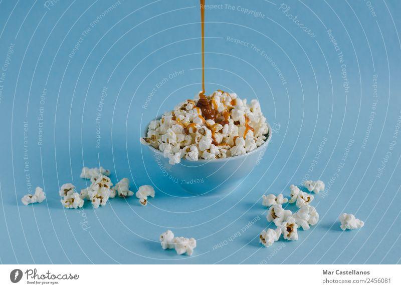 Schüssel mit Popcorn und Karamellsauce auf blauem Hintergrund Getreide Süßwaren Ernährung Essen Schalen & Schüsseln Freizeit & Hobby Tisch Party Veranstaltung