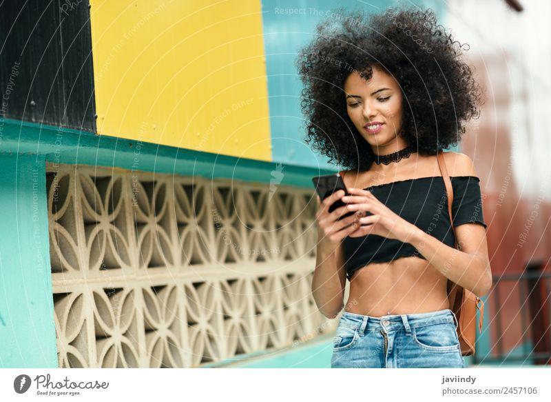 Frau mit Afro-Haaren auf der Straße, die ein Smartphone hält. Lifestyle Stil Freude Glück schön Haare & Frisuren Telefon PDA Technik & Technologie Mensch