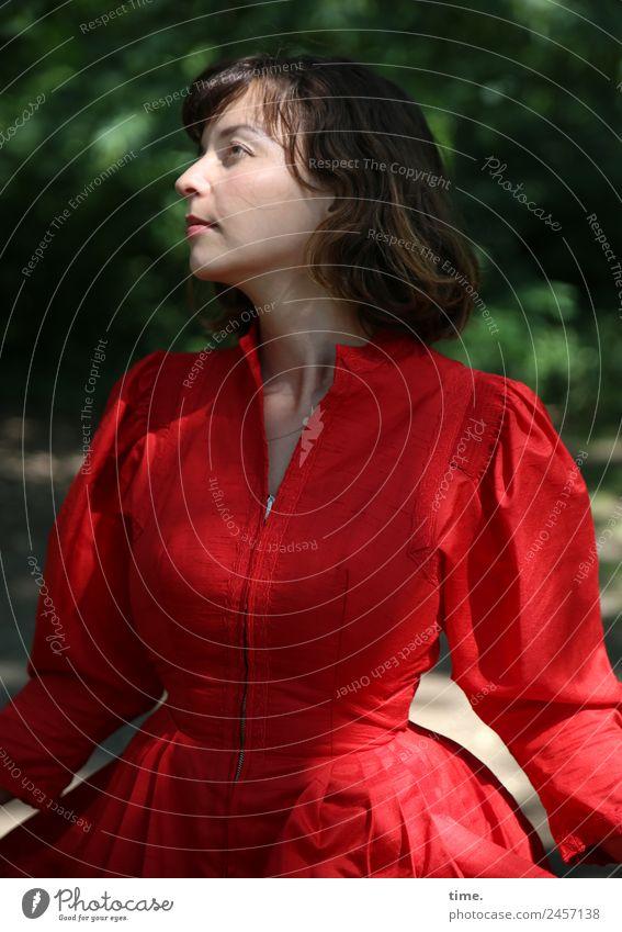 Ulreka feminin Frau Erwachsene 1 Mensch Schönes Wetter Park Kleid brünett langhaarig Pony beobachten drehen Blick stehen rot selbstbewußt Wachsamkeit