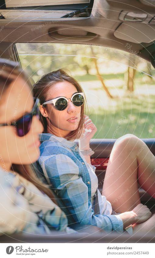 Zwei junge Frauen, die im Auto sitzen und sich ausruhen. Lifestyle Freude Glück schön Erholung Freizeit & Hobby Ferien & Urlaub & Reisen Ausflug Sommer Sonne