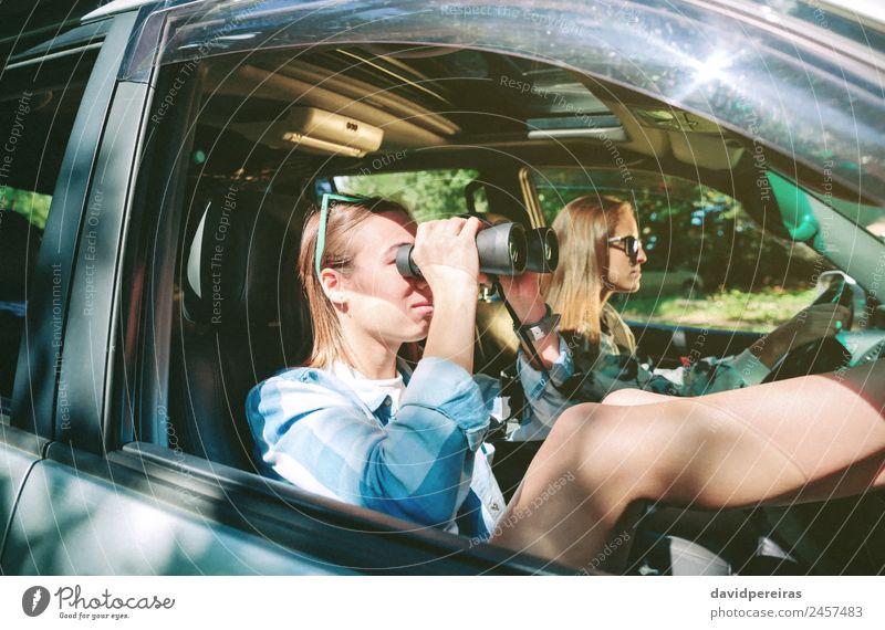 Frau, die durch das Fernglas schaut und eine Freundin fährt. Lifestyle Glück schön Erholung Freizeit & Hobby Ferien & Urlaub & Reisen Ausflug Mensch Erwachsene