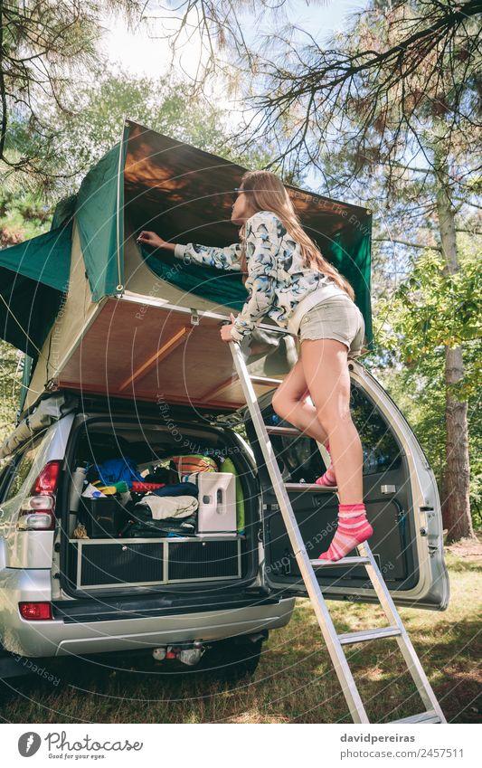 Frau steht in einer Leiter und öffnet das Zelt über dem Auto. Lifestyle Freude Glück Erholung Freizeit & Hobby Ferien & Urlaub & Reisen Ausflug Abenteuer