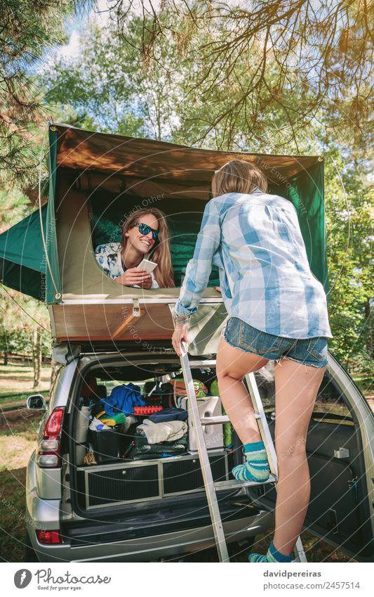 Frau geht die Leiter hinauf, um über dem Auto zu zelten. Lifestyle Freude Glück Erholung Freizeit & Hobby Ferien & Urlaub & Reisen Ausflug Abenteuer Camping