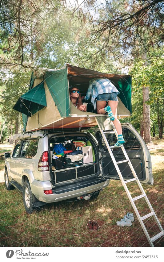 Frau geht die Leiter hinauf, um über dem Auto zu zelten. Lifestyle Freude Glück Freizeit & Hobby Ferien & Urlaub & Reisen Ausflug Camping Sommer wandern