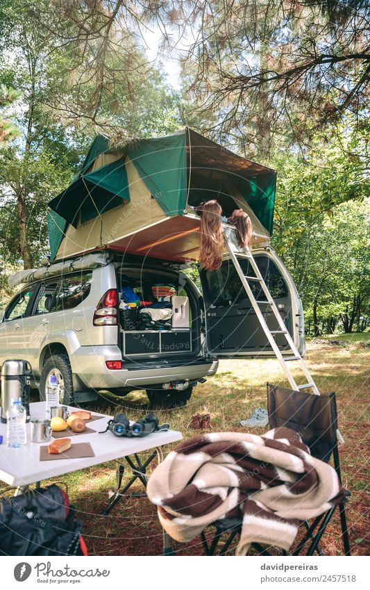 Frauen, die im Zelt über dem Auto liegen und die Natur betrachten. Lifestyle Freude Glück Erholung Freizeit & Hobby Ferien & Urlaub & Reisen Ausflug Abenteuer